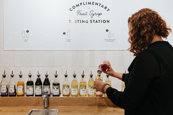 A woman pouring syrup inside the complimentary tasting station.