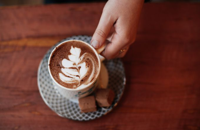 A hand holding a hot chocolate on a table at Rollickin cafe Christchurch.