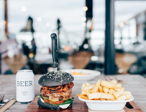 A burger, chips and beer sitting on a table in Ten27 Christchurch cafe.