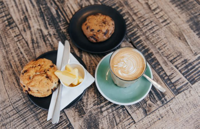 A flatlay of scones and coffee on a table at Little Poms.