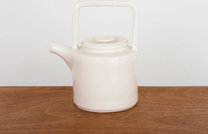 A tea pot on a table.