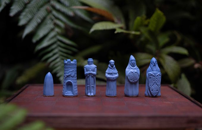 Little blue chess figurines on a table.
