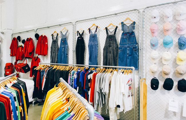 Denim overalls and hats on a wall at Emporium Vintage Boutique Wellington.