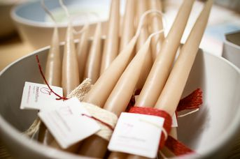 Cream coloured candles with red ribbon in a bowl.