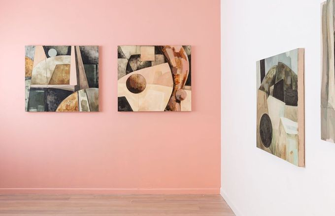paintings hung on a pink wall inside McLeavey gallery.