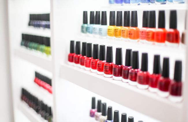 Wall of nail polish on white shelves.