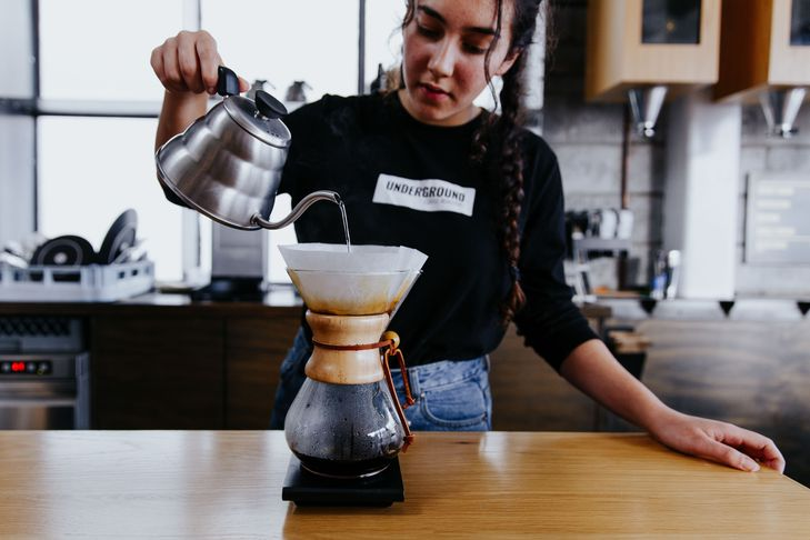 A barista pouring water into a Chemex.