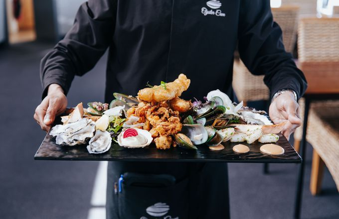 A waiter holding a platter of seafood at Oyster Cove in Southland.
