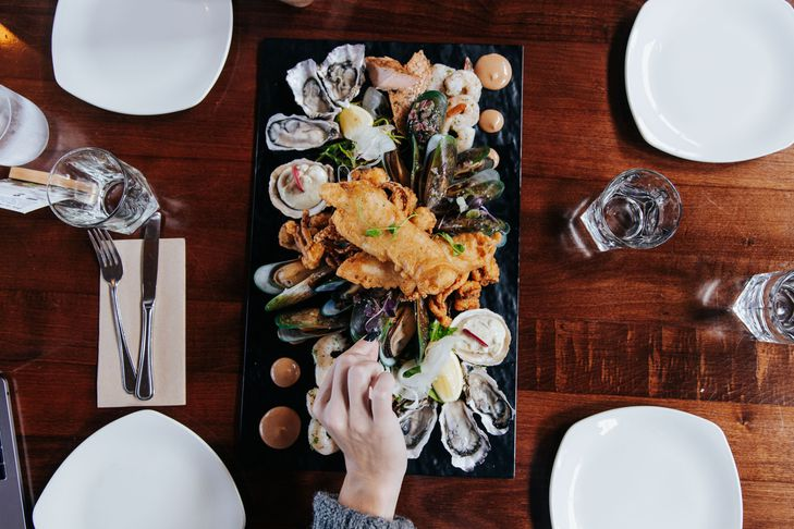 A hand reaching for a seafood platter at Oyster Cove in Southland.