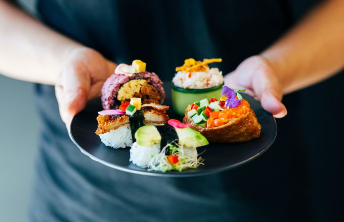 Staff holding a plate of sushi at Rice and Paper Christchurch.