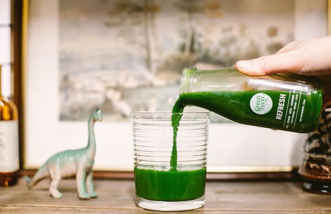 A photo of a woman pouring a Greenroots green juice into a glass.