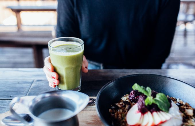 A hand holding a green juice at Lyttelton Coffee Company.