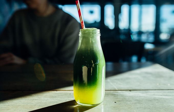 A bottle of green juice with a straw at Dose Diner Christchurch.