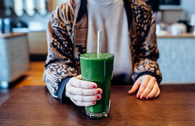 A woman holding a green smoothie at Allpress Christchurch.