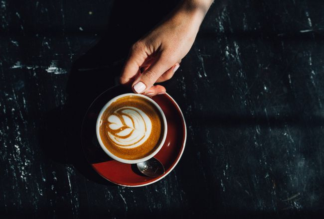 A hand holding a coffee.