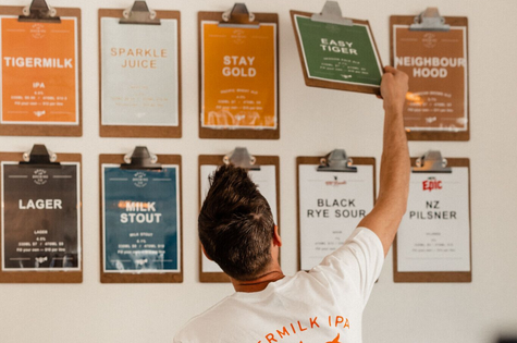 A man organising beer signs inside Brave Brewing Hastings.