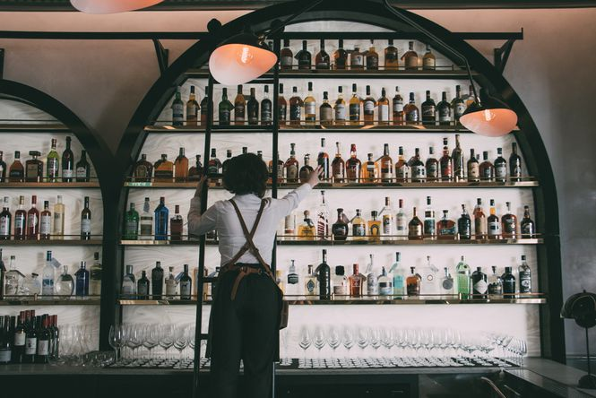 A bar woman reaching for a bottle of liquor.