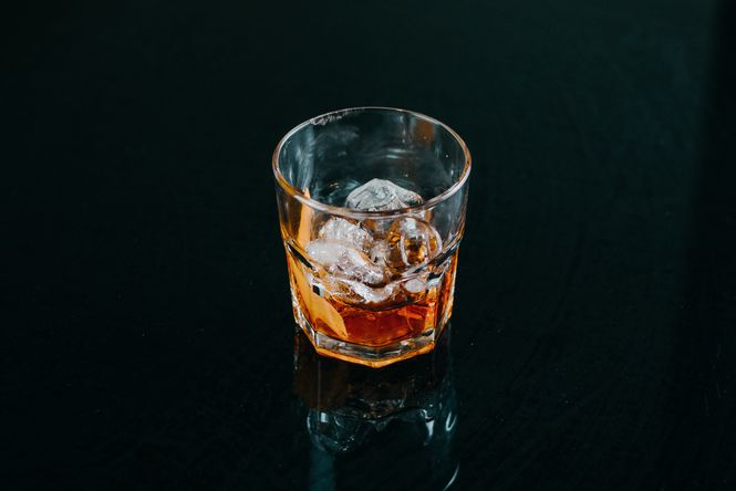A glass of whisky set against a black backdrop.