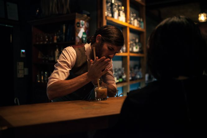 A bar man making a cocktail.
