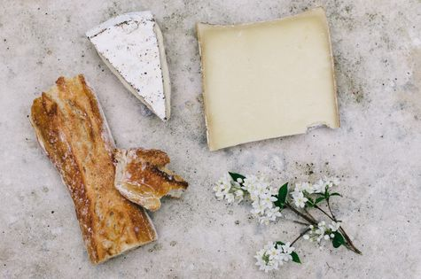 Cheese and bread on a table with flowers.