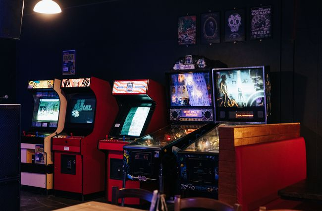 Arcade games lined up against a wall.