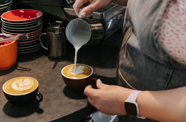 Barista pouring steamed milk into coffee cup.