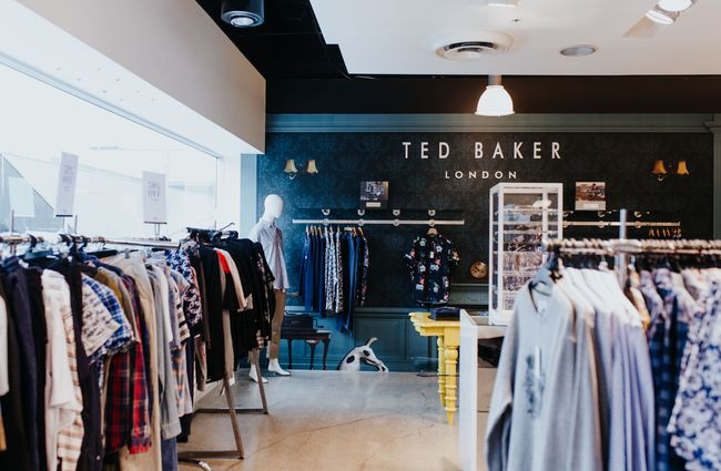 Ted Baker clothing display against a black wall.