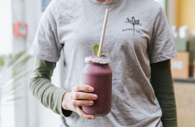 A staff member holding a purple smoothie.