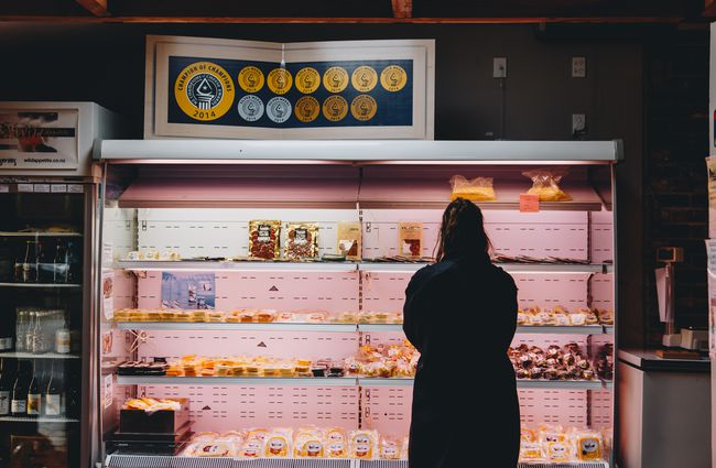 A woman browsing the cheese inside the shop at at Barrys Bay Cheese, Akaroa.