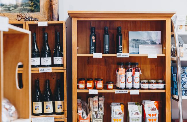Wine and pantry goods on a shelf in the shop at at Barrys Bay Cheese, Akaroa.