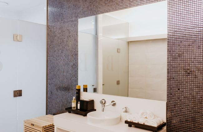 Bathroom with tall mirror and tiles.