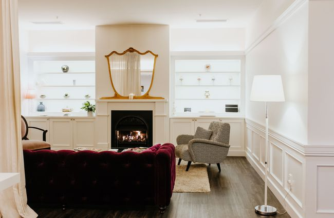 Fireplace with couches and mirror above.