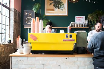 Yellow coffee machine with ice-cream on it.