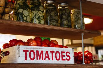 Red tomatoes sign on a white crate on a shelf.