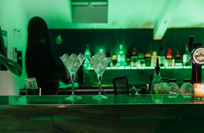 Two martini glasses with ice sit on the bar counter.