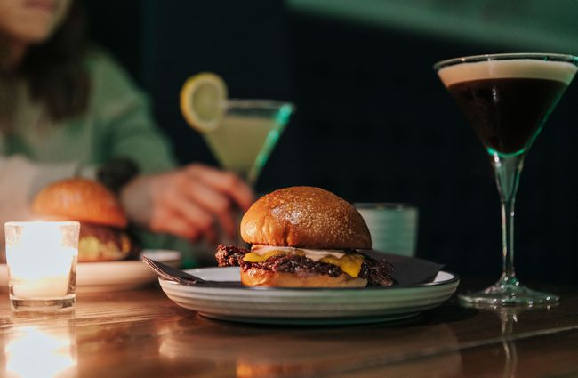 Close up of a burger and martini on a table.