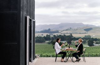 Two women dining outside the entrance to Black Estate.