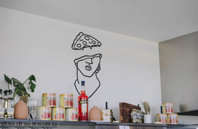 A pizza head illustration on a wall.