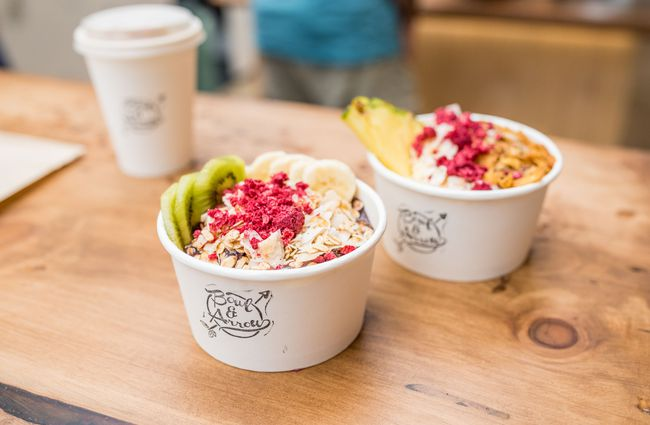 Two bright coloured smoothie bowls in white containers.