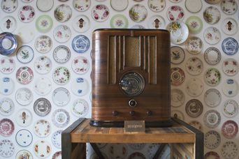 Retro radio against plate wallpaper.
