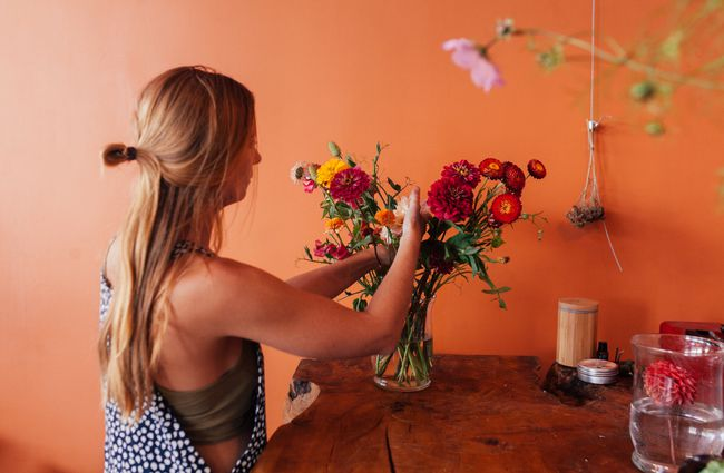 Woman arranging flowers against a tangerine wall.
