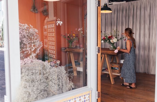Woman arranges flowers inside the doorway of a shop.