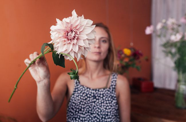 Woman's face partially hidden by a pink flowers.