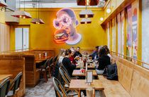 Yellow wall with woman eating a burger mural.