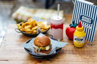 Burger, milkshake and fries on a wooden table.