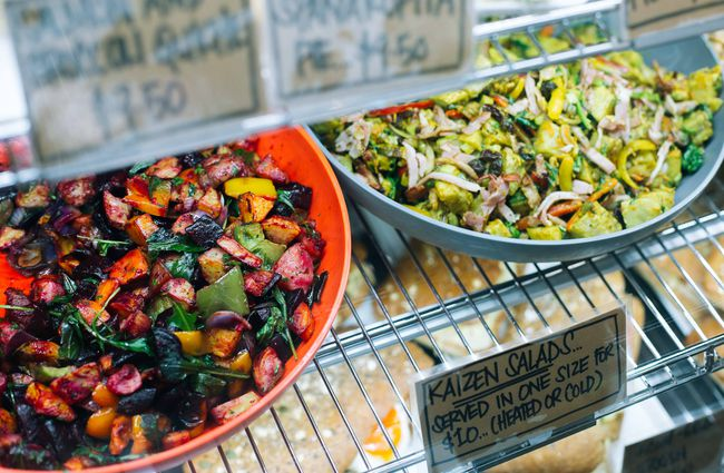 Bowls of coloured salads in a cabinet.