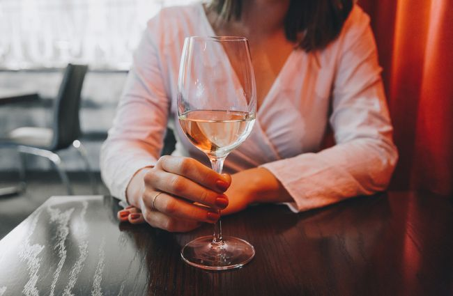 A woman holding a glass of wine.
