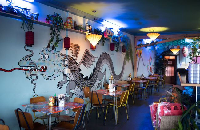 Dragon artwork on a blue wall behind dine in tables.