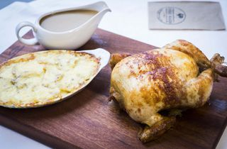 A cooked chicken on a chopping board at Chook Wagon Wellington.