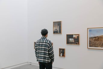 Man viewing paintings.